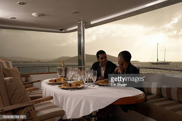 Mature businesspeople dining on deck of yacht, sunset