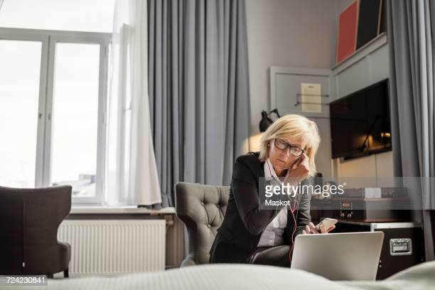 Mature businesswoman adjusting headphones sitting in front of laptop at hotel room