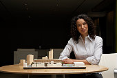 Mature businesswoman by architectural model, smiling, portrait