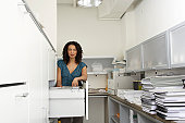 Mature businesswoman by filing cabinet in office, portrait