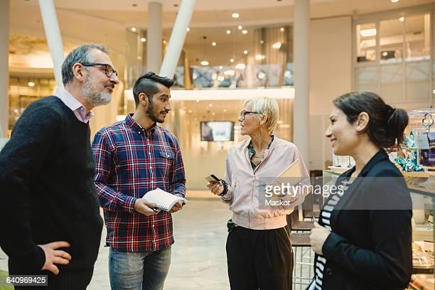 Mature businesswoman holding credit cards while discussing with colleagues in office