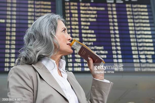 Mature businesswoman holding passport standing by departure board