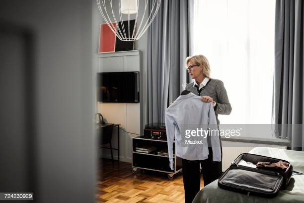 Mature businesswoman holding shirt against window at hotel room