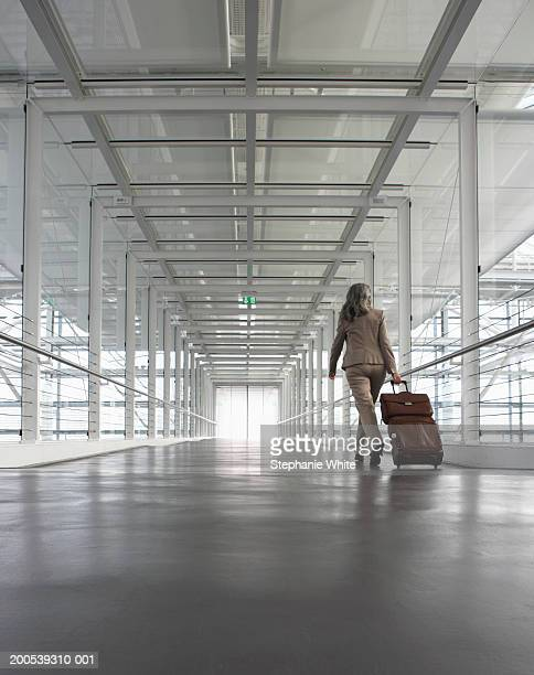 Mature businesswoman in airport, pulling luggage, rear view