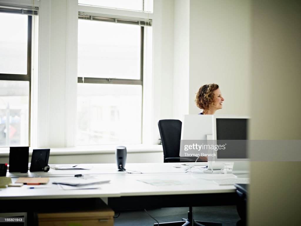 Mature businesswoman in discussion at workstation : Stock Photo