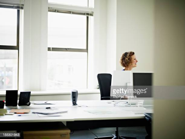 Mature businesswoman in discussion at workstation