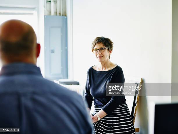 Mature businesswoman in discussion with coworkers