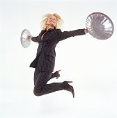 Mature businesswoman jumping, holding out two dustbin lids, smiling
