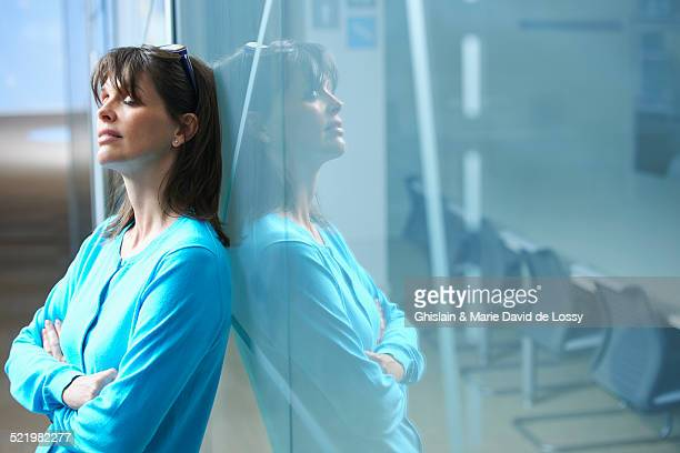 Mature businesswoman leaning against glass wall in office with eyes closed