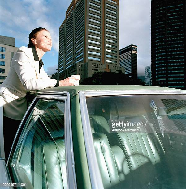 Mature businesswoman leaning on car roof, smiling