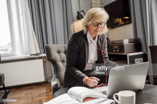 Mature businesswoman listening to headphones while using laptop in hotel room