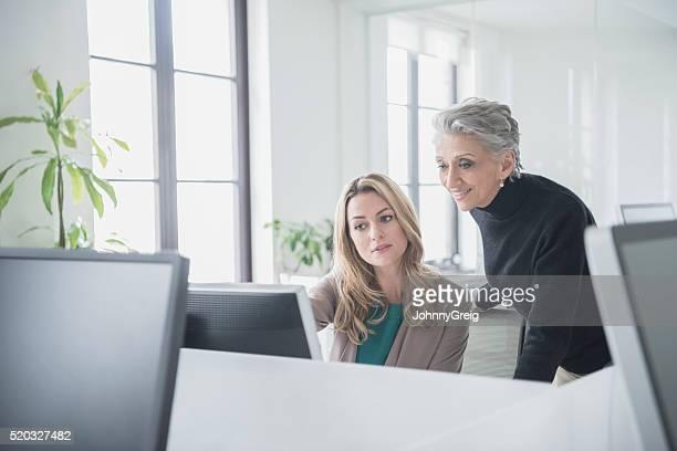 Reife Geschäftsfrau schaut an Computer mit Kollegen