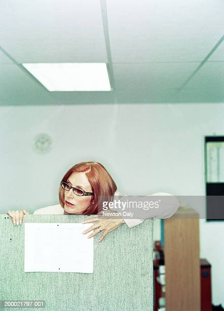 Mature businesswoman looking over partition
