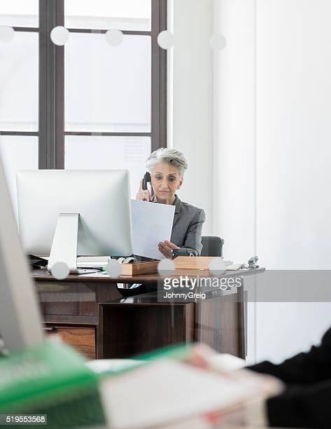 マチュアビジネスウーマンに電話を備えたデスクで、書類