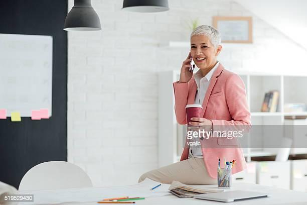 Mature femme d'affaires au téléphone à son bureau.
