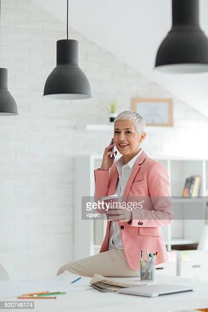 Matura Donna d'affari al telefono nel suo ufficio.