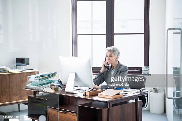 仕事一色マチュア電話中を見ているコンピュータ