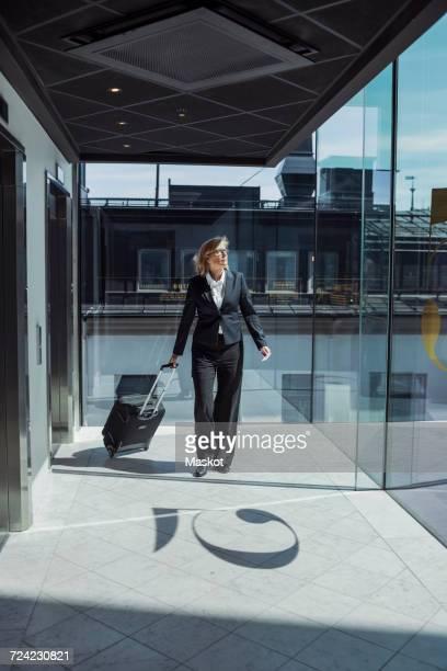 Mature businesswoman pulling wheeled luggage in hotel corridor