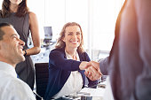 Mature businesswoman shaking hands with other businessman. Business people shaking hands during a meeting. Handshake confirmation done by partners for signing a deal.