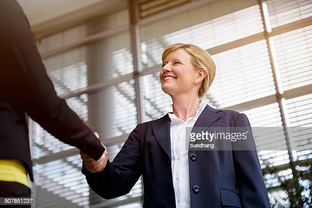 Mature businesswoman shaking hands with client