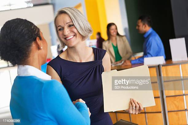 Mature businesswoman shaking hands with prospective employee at job fair