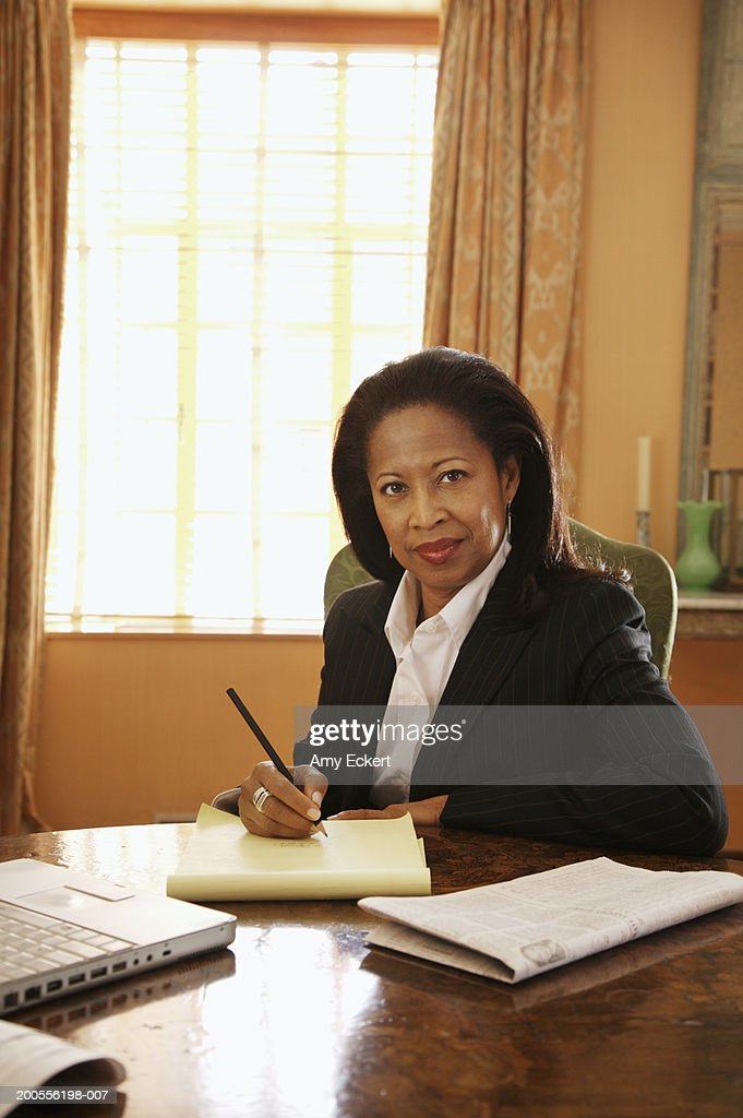 Mature businesswoman sitting at desk in office, portrait : Stock Photo