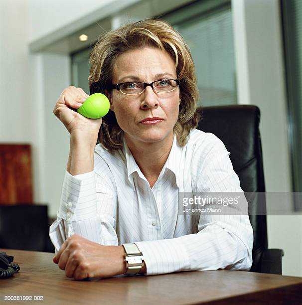 Mature businesswoman sitting at desk using stress ball