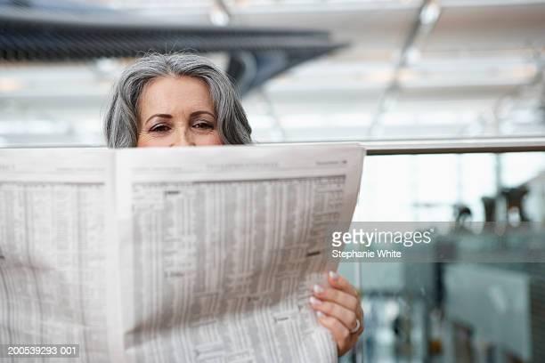 Mature businesswoman sitting in airport reading newspaper