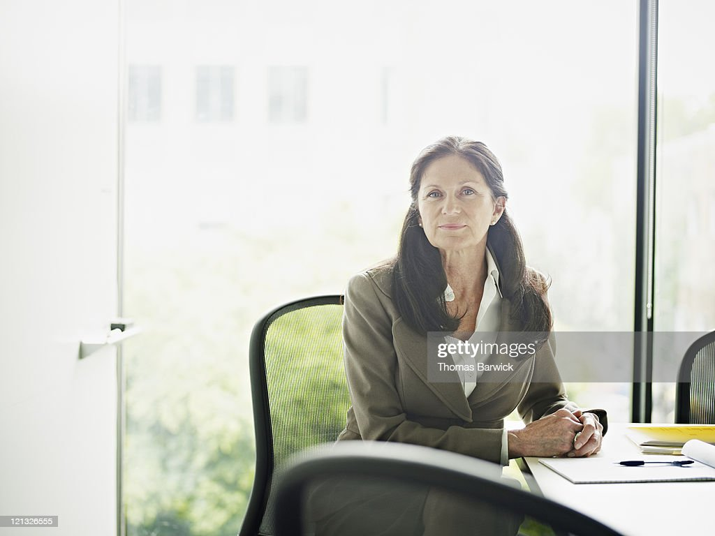 Mature businesswoman sitting in conference room : Stock Photo