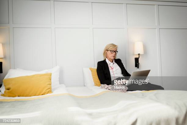 Mature businesswoman sitting on bed using laptop against wall at hotel room