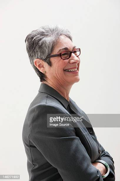 Mature businesswoman smiling, studio shot
