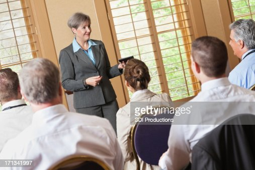 Mature businesswoman speaking to group of professionals