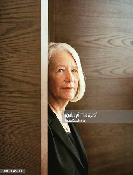Mature businesswoman standing by doorway, portrait