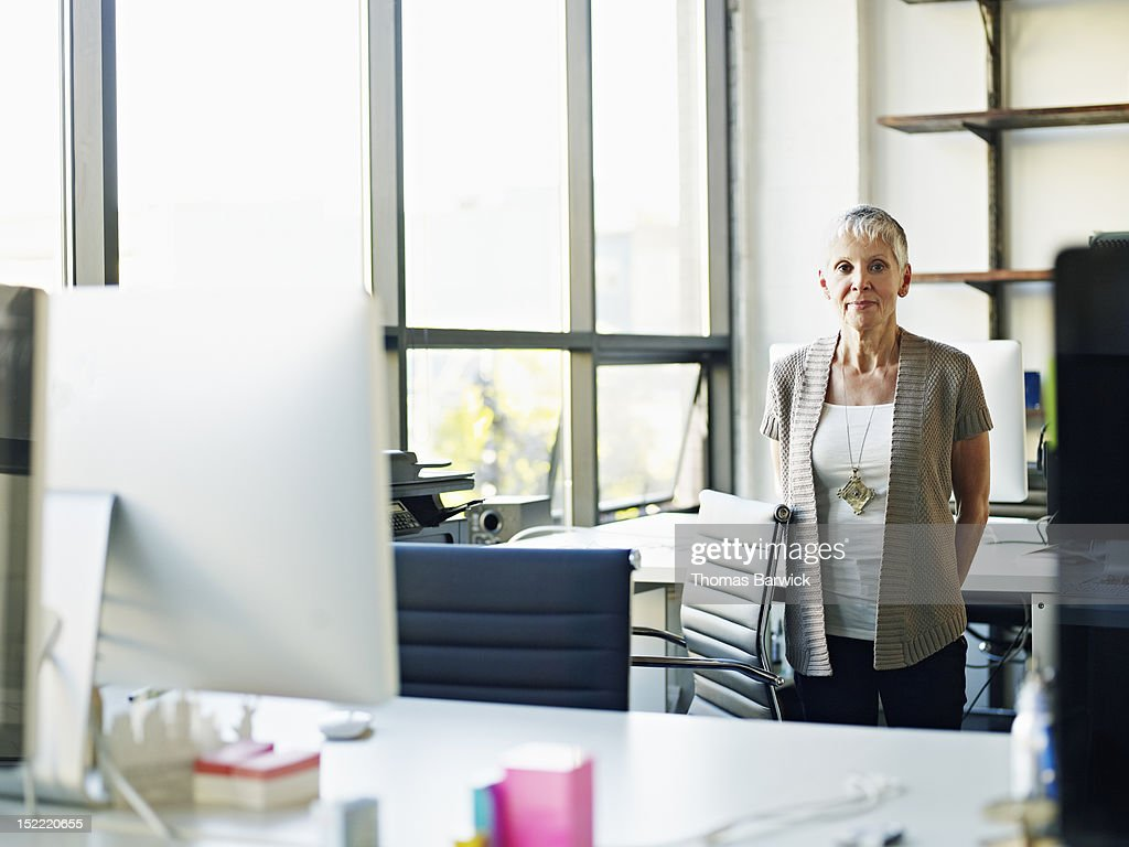 Mature businesswoman standing in high tech office : Stock-Foto