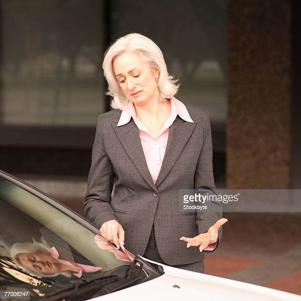 Mature businesswoman taking out parking ticket put under wiper