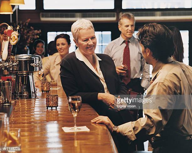 Mature Businesswoman Talking to a Colleague in a Bar