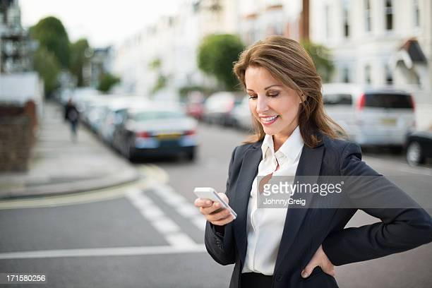 Mature Businesswoman Text Messaging On Mobile Phone