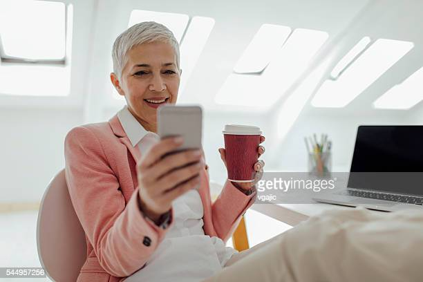 Mature Businesswoman Texting In Her Office.