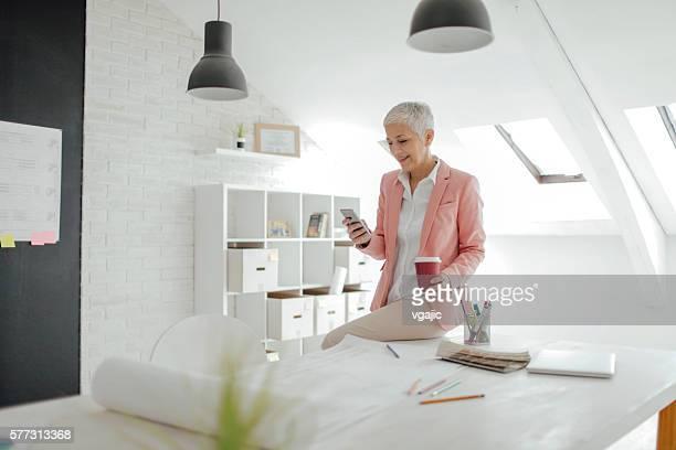 Matura donna d'affari SMS nel suo ufficio.