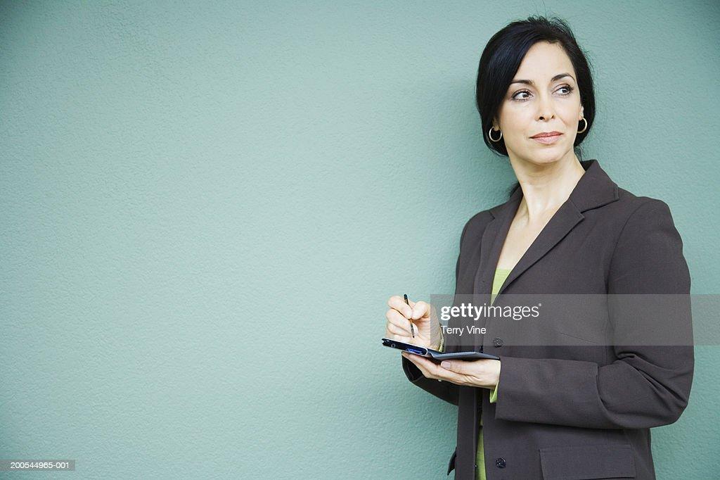 Mature businesswoman using palmtop, looking away