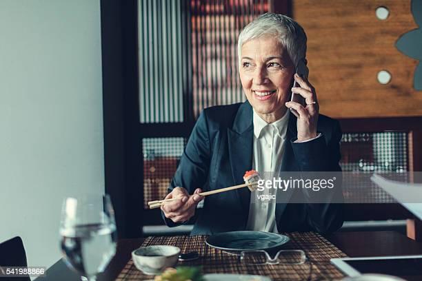 Mature Businesswoman Using Phone In Restaurant.