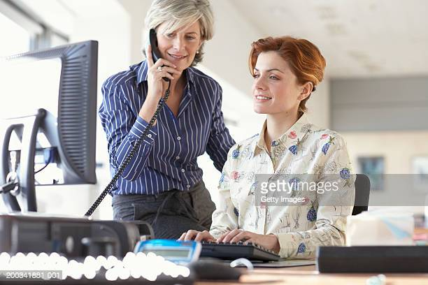 Mature businesswoman using telephone by female colleague at desk