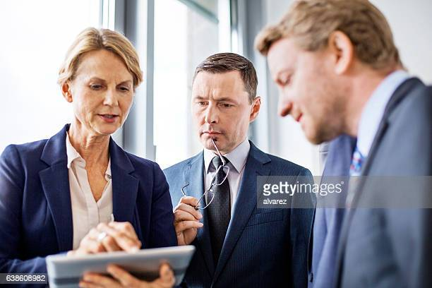 Mature businesswoman viewing proposal to colleagues