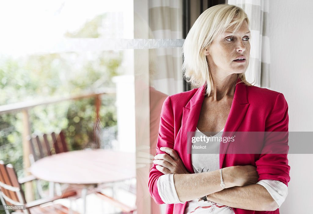 Mature businesswoman with arms crossed standing at office