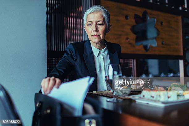 Mature Businesswoman Working and Having Lunch In Restaurant.