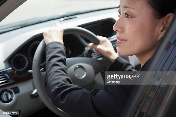 Mature businesswomen driving car.