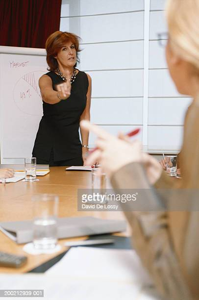 Mature businesswomen gesturing to colleague at business meeting