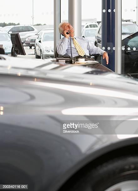 Mature car salesman sitting at desk, using telephone, smiling