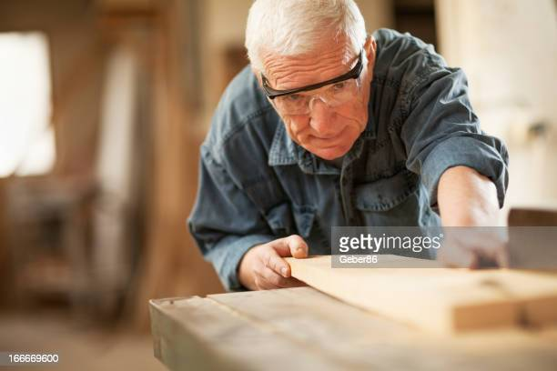 Mature carpenter cutting wooden plank