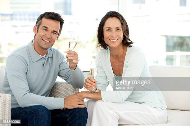 Mature Caucasian Couple celebrating with Champagne